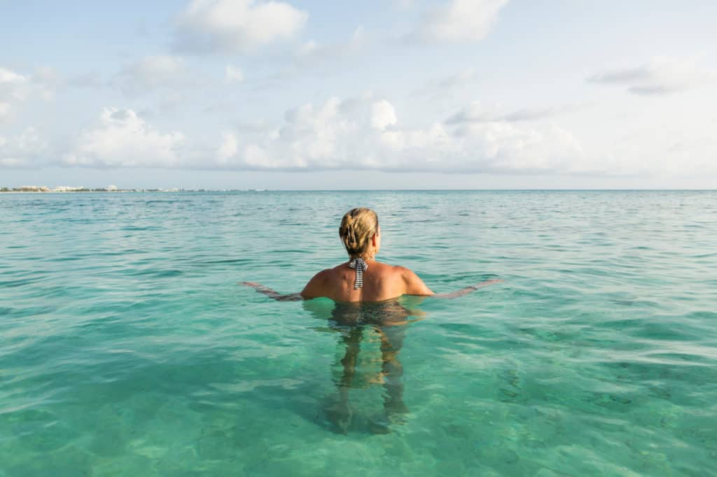 adult-woman-standing-in-ocean-water-at-sunset-PVRUYWU